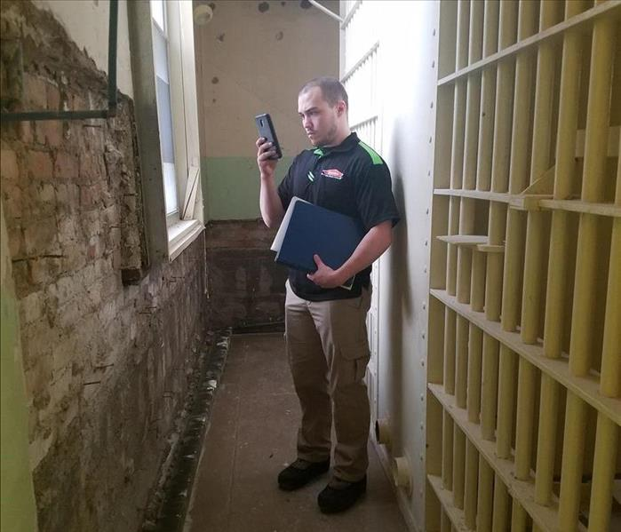 Jail cell wall with technician inspecting damage